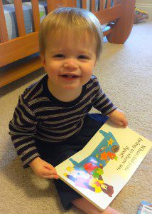"""Henry, 19 months, reads an interactive book. Interactive books like """"Where's Spot"""" or """"Where's Baby's Belly Button"""" are popular with this crowd."""