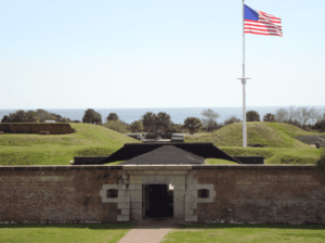 Brick Facade Fort Moultrie Sullivans Island in foreground with American Flag waving in background